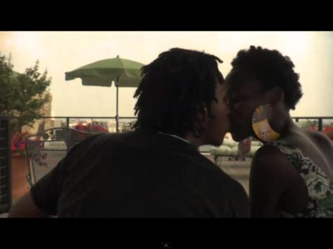 Dark-skinned woman & medium-skinned man kissing
